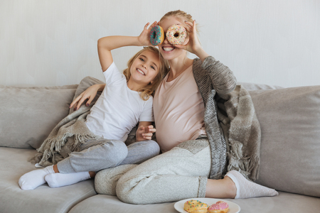 happy pregnant mother and daughter covering eyes with donuts