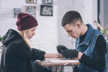 Tattoo master in gloves working on arm piece in studio