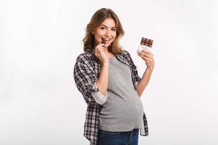 young pregnant woman eating chocolate and smiling at camera isolated on white