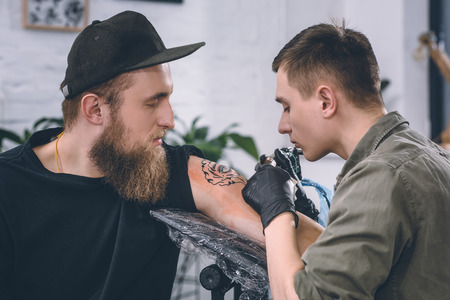 Tattoo artist and bearded man during tattooing process in studio