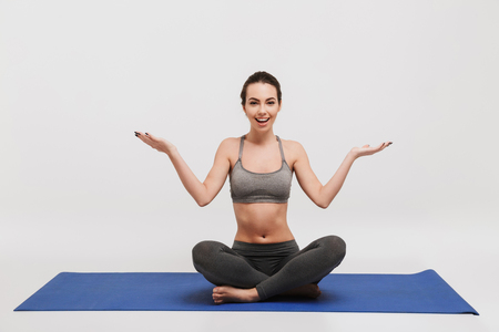 bewildered emotional young woman sitting on yoga mat isolated on white