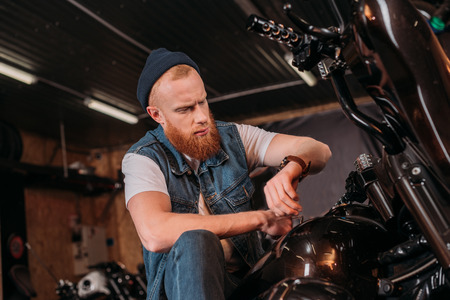 young man looking at watch while sitting on motorcycle at garage