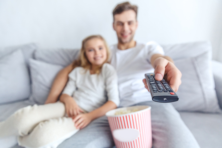 close-up shot of father and daughter using tv remote control at home Stock Photo