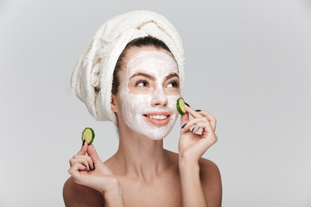 young woman with facial skincare mask and cucumber slices isolated on white