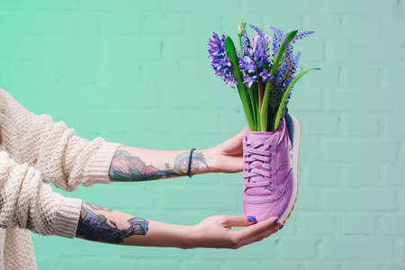 cropped image of girl holding shoe with hyacinth flowers Stock Photo