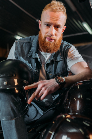 handsome young man sitting on bike with helmet at garage Imagens