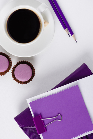 top view of workspace with coffe cup and cupcakes