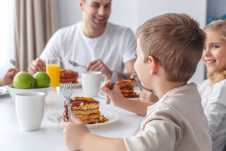 adorable little kids having breakfast with father