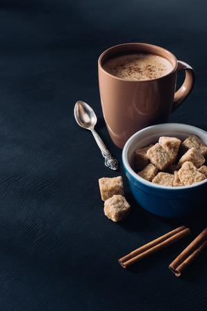 close up view of cup of coffee, bowl with brown sugar and cinnamon sticks on dark surface