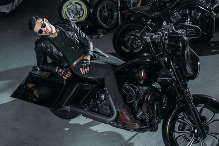 high angle view of handsome young man in leather jacket lying on bike at garage Stock Photo