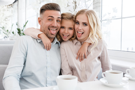 happy young family making grimaces in cafe while looking at camera