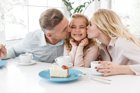 parents kissing their happy little daughter while spending time in cafe
