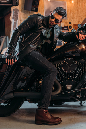 handsome young man in stylish clothing sitting on motorcycle at garage
