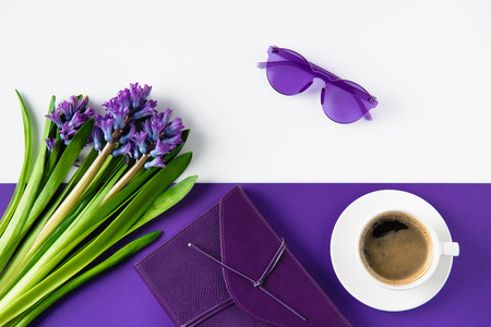 top view of bouquet of purple hyacinth flowers and cup of coffee on table