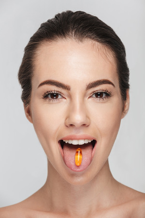 attractive young woman with fish oil capsule in mouth isolated on white