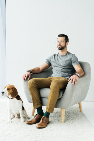 man sitting on armchair and dog sitting on floor