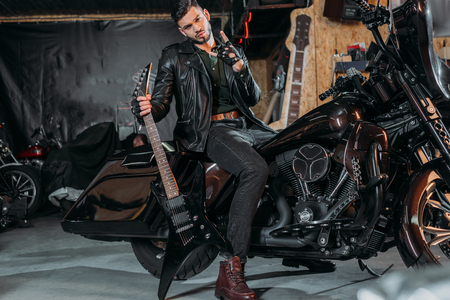 stylish young man in leather jacket sitting on bike with electric guitar at garage