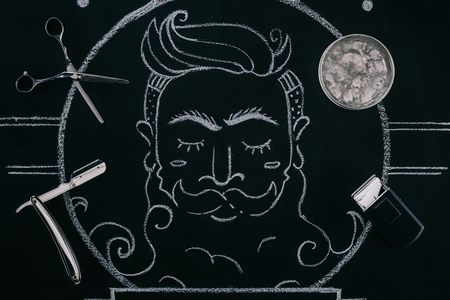 top view of arranged ice cubes in bowl, scissors, razor and drawn picture on blackboard Stock Photo