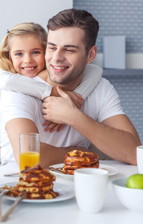 daughter embracing her father from behind while he having breakfast