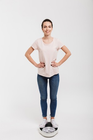 young woman standing on scales with arms akimbo isolated on white Stock Photo - 111742304