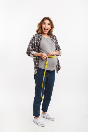 excited pregnant woman measuring tummy with measuring tape isolated on grey Фото со стока