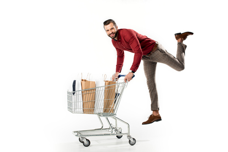 smiling man with shopping cart full of shopping bags and jacket isolated on white