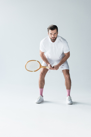 handsome tennis player with tennis racket on grey