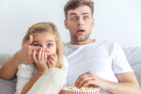 scared father and daughter watching horror movie at home Stock Photo