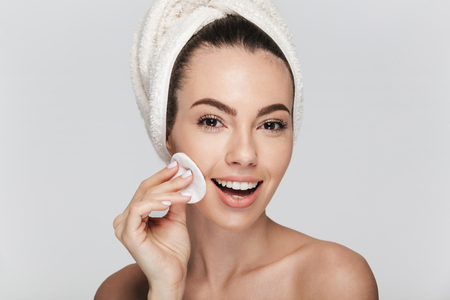 giovane donna pulizia viso con disco di cotone isolato su white