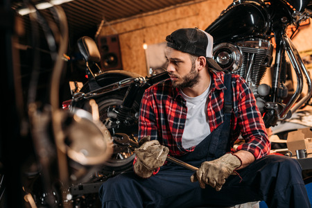 handsome bike repair station worker with wrench sitting in front of motorcycle Imagens