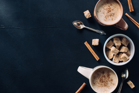 top view of cups of coffee, spoons, bowl of cane sugar and cinnamon stick on dark tabletop