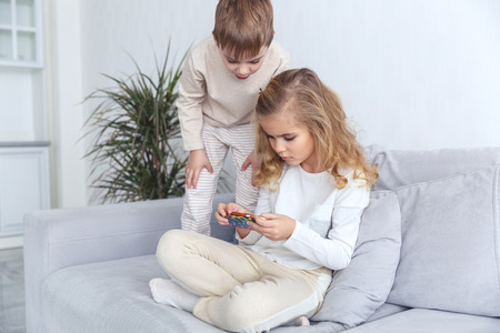 little kids using smartphone together on couch