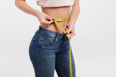 cropped shot of woman measuring her waist isolated on white Imagens