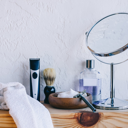 close up view of arranged barber equipment for shaving on wooden shelf Фото со стока
