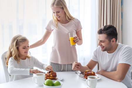 young happy family having breakfast together on weekend morning Imagens