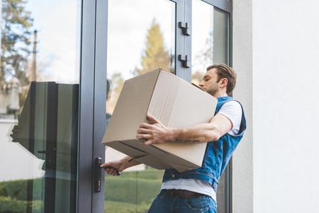 Mann mit Karton, der die Tür des neuen Hauses öffnet Standard-Bild