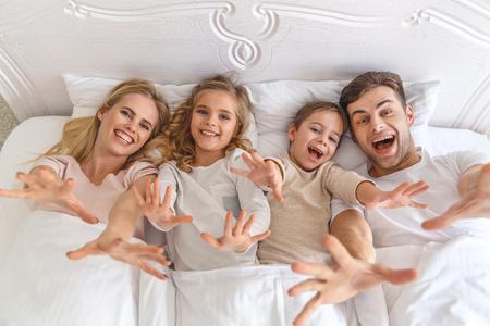 Blick von oben auf die junge Familie, die im Bett nach der Kamera greift