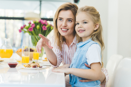 smiling woman showing something mo daughter during breakfast at home