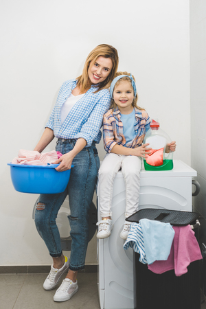 smiling housewife with laundry and little daughter looking at camera at home