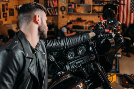 stylish young man in leather on bike at garage Stock Photo