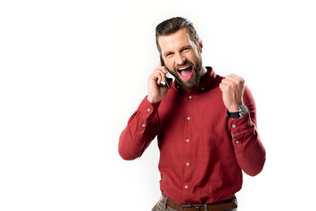 portrait of excited man talking on smartphone isolated on white Imagens