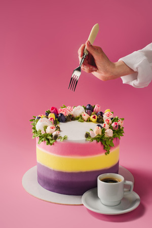 cropped shot of woman with fork, cup of coffee and cake decorated with cream flowers isolated on pink