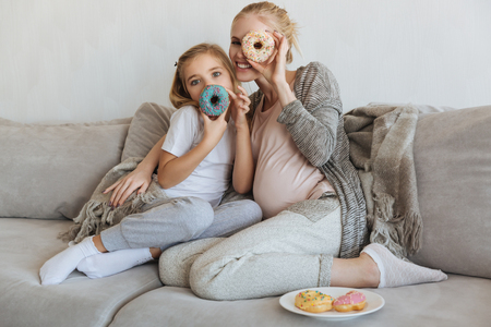 happy pregnant mother and daughter covering faces with donuts
