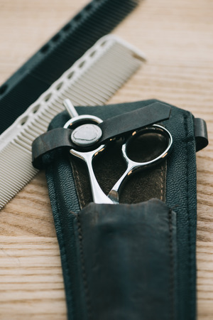 close up view of scissors and combs for hairstyling on wooden tabletop