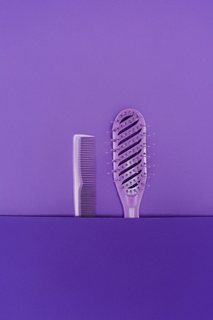 close up view of purple hairbrush and comb isolated on purple Foto de archivo - 111481398