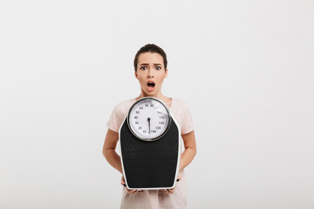 shocked young woman holding scales isolated on white