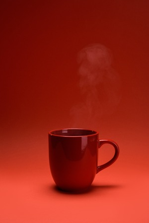 close up view of red cup of coffee isolated on red