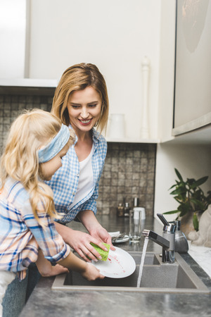 side view of little daughter helping mother to wash dishes after dinner at home