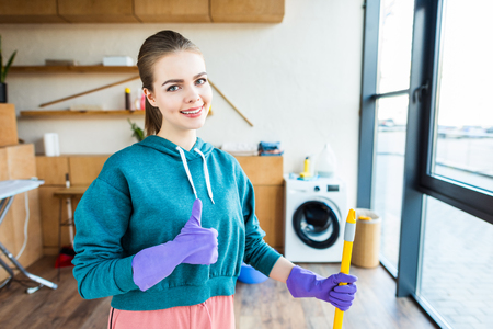 smiling young woman cleaning house with mop and showing thumb up Archivio Fotografico
