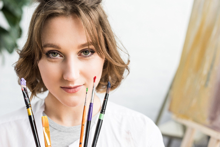 Young inspired girl looking at camera with brushes in hands in light studio